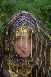 Veiled Innocence. A innocent looking girl wearing a blue head scarf with gold coins and a veil Stock Photography