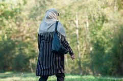 Veiled Muslim woman walking in public garden on back stock images