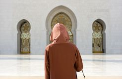 Veiled muslima in mosque. ABU DHABI, UNITED ARAB EMIRATES - DEC 28, 2017: A veiled muslima woman in the Sheikh Zayed Mosque in Abu Dhabi. It is the largest Royalty Free Stock Image