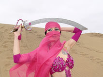 Veiled woman and sabre at desert Stock Photography