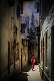 Veiled woman walking through a narrow street Stock Image