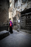 Veiled woman walking through a narrow street Royalty Free Stock Photo