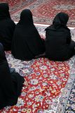 Veiled women in mosque. Veiled women in black dress on Persian carpets in a shiite mosque in Damascus, Syria Stock Photos