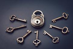 Veiligheid of geheim beschermingsconcept, uitstekend die messingshangslot door veelvoudige sleutels op een donkere zwarte achterg royalty-vrije stock fotografie