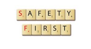 Veiligheids eerste woorden in een houten tegel worden geschikt die stock fotografie