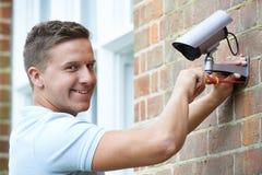 Veiligheidsadviseur Fitting Security Camera aan Huismuur Royalty-vrije Stock Foto