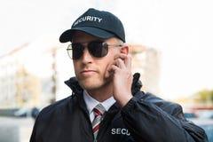 Veiligheidsagent Listening To Earpiece stock foto's