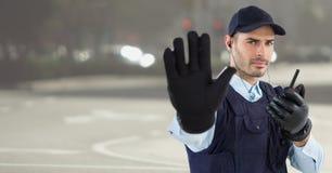 Veiligheidsagent met walkie-talkie en hand omhoog tegen onscherpe straat royalty-vrije stock foto's