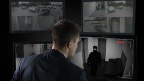 Veiligheidsagent vooraan kabeltelevisie-lengte het letten op bankdiefstal, die politie roepen stock videobeelden