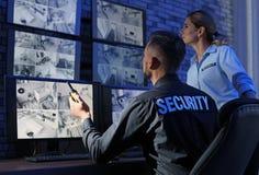Veiligheidsagenten die moderne kabeltelevisie-camera's controleren stock afbeelding