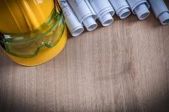 Veiligheidsbril gerolde blauwdrukken en mede bouwvakkerbouw Stock Foto