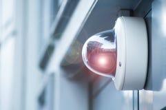 veiligheidscamera bij de moderne bouw met gloed stock afbeeldingen