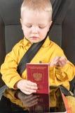 Veiligheidsgordel, paspoort Een gelukkig klein kind zit in de autozetel in het paspoort van een Russische burger Het concept gren Stock Foto