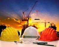 Veiligheidshelm op civiels-ingenieur werkende lijst tegen kraanlift Stock Afbeeldingen
