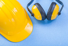 Veiligheidsoorbeschermers die helm bouwen bij de blauwe bouw als achtergrond Royalty-vrije Stock Afbeeldingen