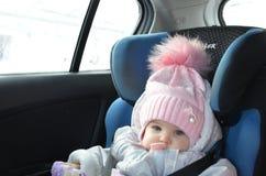 Veiligheidszetel voor baby in auto Weinig leuk meisje in een roze die hoed en overall zit de winter in een kind met riemen wordt  royalty-vrije stock foto