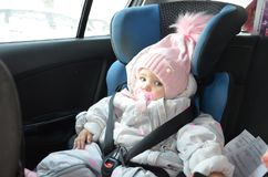 Veiligheidszetel voor baby in auto Weinig leuk meisje in een roze die hoed en overall zit de winter in een kind met riemen wordt  royalty-vrije stock afbeelding