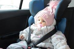Veiligheidszetel voor baby in auto Weinig leuk meisje in een roze die hoed en overall zit de winter in een kind met riemen wordt  stock foto's