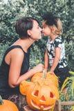 Veille de la toussaint Baisers de fille et de mère près de cric-o-lanterne dans le jardin Décoration pour la partie famille Photo Image libre de droits