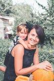 Veille de la toussaint Fille étreignant la mère près de la cric-o-lanterne dans le jardin Décoration pour la partie Famille heure Photos stock