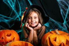 Veille de la toussaint heureuse Jolie fille de petit enfant dans le costume de sorcière avec découper le potiron Famille heureuse images stock