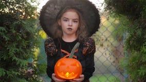 Veille de la toussaint La fille mignonne montre une sorcière gaie Elle est habillée dans une robe et un chapeau noirs Fille tenan clips vidéos
