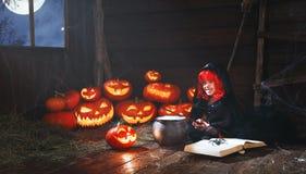 Veille de la toussaint petit enfant de sorcière faisant cuire le breuvage magique avec le potiron et photographie stock
