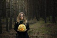 Veille de la toussaint Potiron jaune Belle fille dans une robe noire dans la forêt images stock