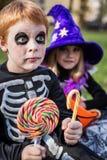 Veille de la toussaint Squelette et sorcière tenant les sucreries colorées Images libres de droits