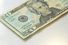 Veinte dólares con una nota 20 dólares Foto de archivo