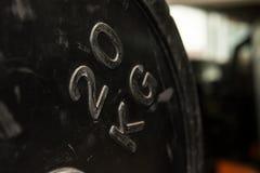 Veinte kilogramos de peso redondo en un gimnasio Equipo del entrenamiento imagenes de archivo