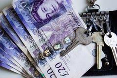 Veinte libras de rollo del dinero con llaves de la casa en un tenedor dominante en una tabla fotos de archivo