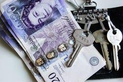 Veinte libras de rollo del dinero con llaves de la casa en un tenedor dominante en una tabla foto de archivo