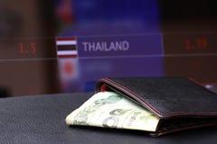 Veinte THB tailandeses del billete de banco del baht en cartera negra en piso negro y el tablero digital de fondo del dinero del  imagen de archivo libre de regalías