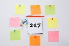 Veinticuatro horas y 7 días a la semana El concepto escribe en la tabla de la oficina, la libreta y el lápiz colorido Visión desd Imagen de archivo libre de regalías