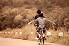 Veiw arrière de jeunes couples des hippies montant une bicyclette ensemble Photos stock