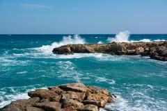 Veiw av vågorna som bryter på stenar med massor av färgstänk driva som fiskar medelhavs- netto havstonfisk royaltyfri foto