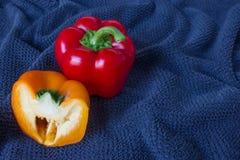 Veiw superior de una pimienta roja y de la pimienta a medias anaranjada en un fondo azul fotos de archivo libres de regalías