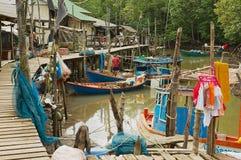 Veja à vila do ` s dos pescadores com as casas do pernas de pau e os barcos de pesca residenciais na maré baixa em Koh Chang, Tai fotos de stock