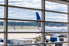 Veja para fora a janela do aeroporto aos aviões e às operações da rampa Fotos de Stock