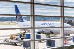 Veja para fora a janela do aeroporto aos aviões e às operações da rampa Fotos de Stock Royalty Free