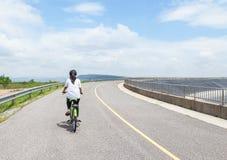 Veja para trás a menina que aprecia o abrandamento da bicicleta do passeio no cume da represa da estrada fotografia de stock