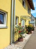 Veja a parte dianteira de propriedade privada com os arbustos cor-de-rosa, as janelas e o telhado imagem de stock