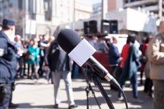 vektor för protest för demonstrationsillustration proper Mikrofon i fokusen, suddiga personer som protesterar i bakgrund Arkivbilder