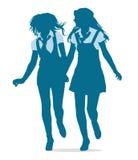 Silhouettes av tonårs- skolar flickaspringtogeth Arkivfoto