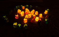 A vela amarela e verde brilhante ilumina-se na obscuridade fotografia de stock royalty free