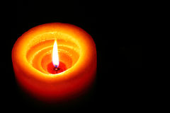 Vela anaranjada que brilla en la oscuridad con el espacio negro de Backround a la derecha Fotografía de archivo libre de regalías