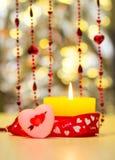 Vela ardente amarela bonita do dia de Valentim do St ao lado de um coração vermelho e de uns grânulos vermelhos Fotografia de Stock Royalty Free