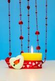 Vela ardente bonita do dia de Valentim do St ao lado de um coração e de uns grânulos vermelhos Fotografia de Stock Royalty Free