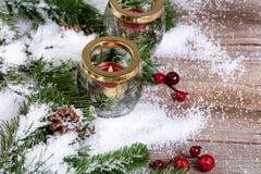 A vela ardente com abeto nevado ramifica em placas de madeira rústicas fotos de stock royalty free
